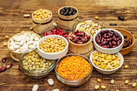 Set of various dry legumes in bowls, indispensable protein for a healthy lifestyle. Assorted different types of beans. Wooden table background, close up