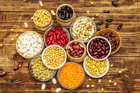 Set of various dry legumes in bowls, indispensable protein for a healthy lifestyle. Assorted different types of beans. Wooden table background, top view 免版税图像