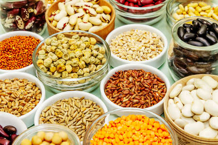Assorted different types of beans and cereals grains. Set of indispensable sources of protein for a healthy lifestyle. Light green background, close up