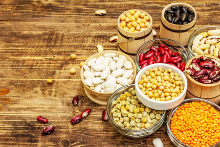 Set of various dry legumes in bowls, indispensable protein for a healthy lifestyle. Assorted different types of beans. Wooden table background, copy space 免版税图像