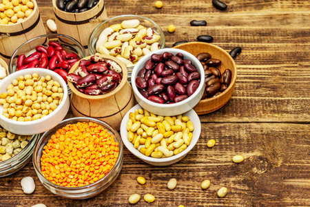 Set of various dry legumes in bowls, indispensable protein for a healthy lifestyle. Assorted different types of beans. Wooden table background, copy space Foto de archivo