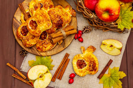 Homemade delicious apple dessert. Fresh sweet bakery, portioned puffs. Fragrant cinnamon sticks, ripe apples, autumn foliage, sea salt. Wooden boards table, top view