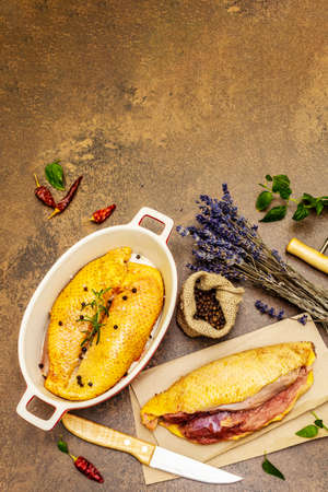 Preparation raw duck with sea salt, fresh rosemary, black peppercorn, dry lavender and wine. Poultry meat, natural BIO product, domestic fowl. Provence style, stone background, top view