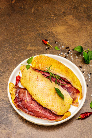 Raw duck with fresh greens and fragrant spices. Poultry meat, natural BIO product, domestic fowl. Stone concrete background, top view