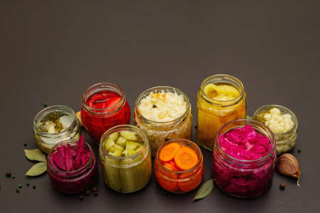 Assorted of fermented vegetables in glass jars. Preserved season vegetables concept, probiotics food for healthy lifestyle. Black stone concrete background, copy space