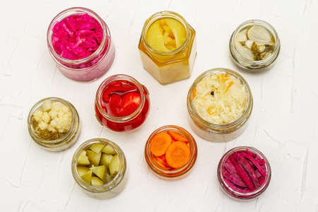 Assorted of fermented vegetables in glass jars. Preserved season vegetables concept, probiotics food for healthy lifestyle. White putty background, top view