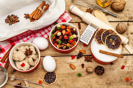 Christmas baking background 2021. Traditional Saxon Stollen with fruits and nuts. Food Ingredients for New Year cooking. Festive decor, wooden boards, top view