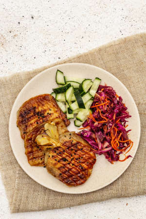 Healthy Paleo food with grilled meat, fresh cucumber, fermented cabbage and carrot. Ketogenic diet concept. Stone concrete background, top view