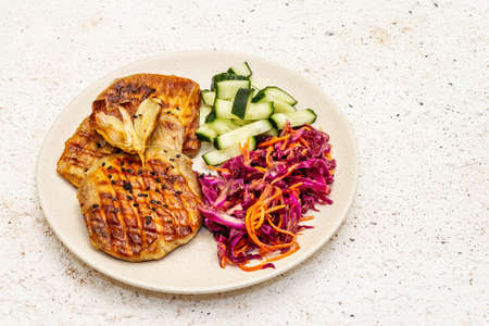 Healthy Paleo food with grilled meat, fresh cucumber, fermented cabbage and carrot. Ketogenic diet concept. Stone concrete background, close up