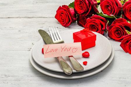 浪漫的晚餐桌。情人节或母亲节,婚礼餐具的概念。新鲜的伯根地玫瑰花束,白色葡萄酒木板背景