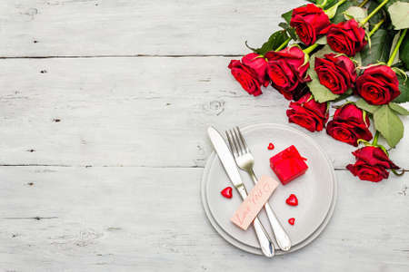 Romantic dinner table. Love concept for Valentine's or mother's day, wedding cutlery. Bouquet of fresh burgundy roses, white vintage wooden boards background