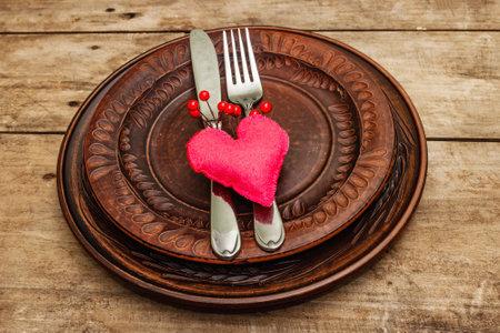 浪漫的晚餐桌。情人节或母亲节,婚礼餐具的概念。新鲜的伯根地玫瑰花束,葡萄酒木板背景,土气样式
