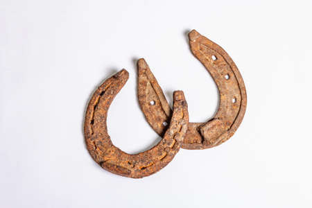 Cast iron metal horseshoes isolated on white background. Good luck symbol, festive concept. Badly worn rusty horse accessories, top view