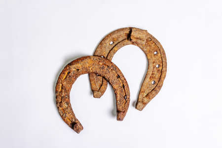 Cast iron metal horseshoes isolated on white background. Good luck symbol, festive concept. Badly worn rusty horse accessories