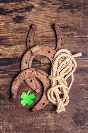 Badly worn horseshoes, rope, and felt clover leaf. Good luck symbol, St. Patrick's day concept. Vintage wooden boards background