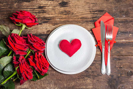 Romantic dinner table. Love concept for Valentine's or mother's day, wedding cutlery. Bouquet of fresh burgundy roses, vintage wooden boards background, top view