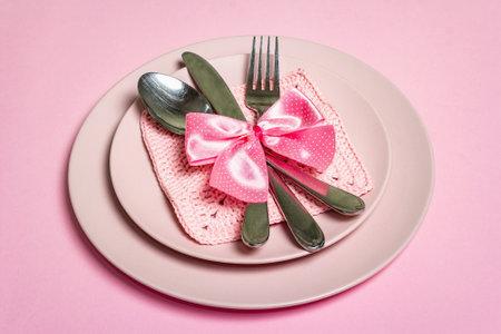 浪漫的晚餐桌。情人节或母亲节,婚礼餐具的概念。简约的风格,玫瑰盘子,钩针编织餐巾,波尔卡点绑弓,文字的地方