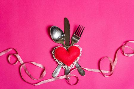 在桃红色颜色的浪漫饭桌。情人节或母亲节,婚礼餐具的概念。手工制作的软毡心,波尔卡点丝带