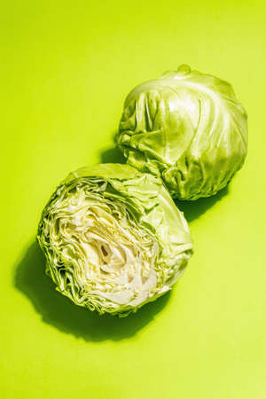Fresh young cabbage, half and whole on bright green background. Modern hard light, dark shadow. Vegetables for cutting spring salad. Vegan food, diet, vitamins