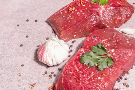 Raw beef steaks on a gray stone background. Trendy hard light, dark shadow. Spices, hot chili, scattered black peppercorn, fresh garlic, and parsley, close up