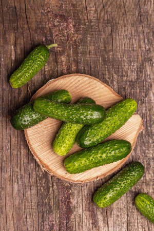 Crispy cucumbers on a wooden stand. Fresh green vegetables, organic farmer product. Wooden chopping board, marble stone background, top view Stockfoto