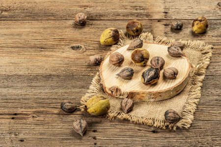 Ripe Juglans cordiformis Maxim or heart-shaped walnut. Young green and unpeeled whole nuts on a stand. Vintage wooden boards background, copy space Stock Photo