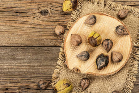 Ripe Juglans cordiformis Maxim or heart-shaped walnut. Young green and unpeeled whole nuts on a stand. Vintage wooden boards, top view background Stock Photo