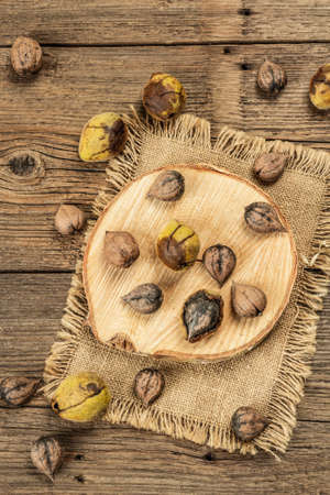 Ripe Juglans cordiformis Maxim or heart-shaped walnut. Young green and unpeeled whole nuts on a stand. Vintage wooden boards, top view background