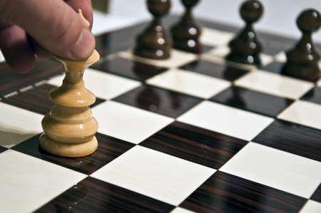 tablero de ajedrez: Mano de hombre mover reina en la tabla de ajedrez