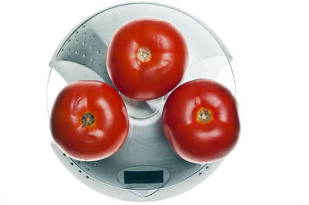 Tomatoes isolated on food scale photo
