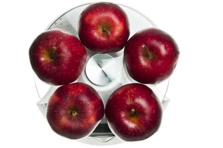 Red apples isolated on food scale photo