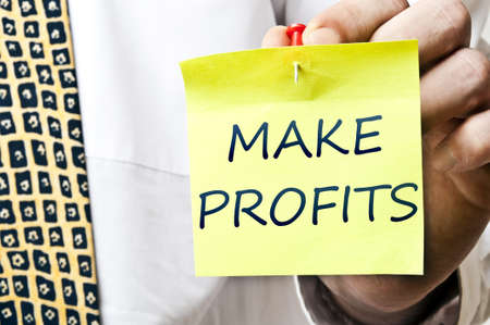 Make profits post it ready to be posted by businessman hand photo