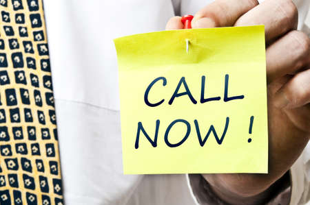 Call now post it in business man hand photo