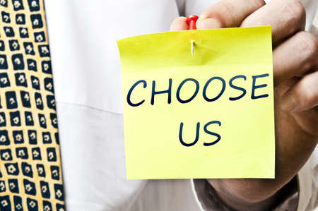 Choose us post it in business man hand photo