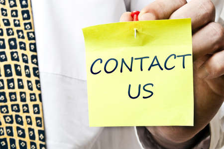 Contact us post it in business man hand photo