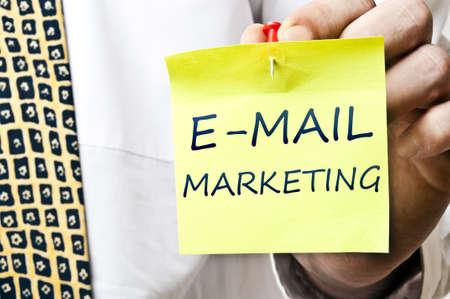 email communication: E-mail marketing post it in business man hand Stock Photo