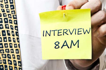 Interview reminder in business man hand photo