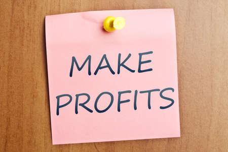 Make profits word  post it on wooden wall photo
