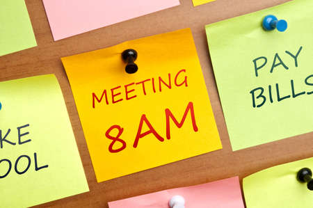 Meeting 8AM post it on wooden wall Stock Photo - 8925556