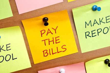 pay wall: Pay the bills words post it on wooden wall