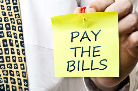 Pay the bills post it in business man hand Stock Photo - 8925613