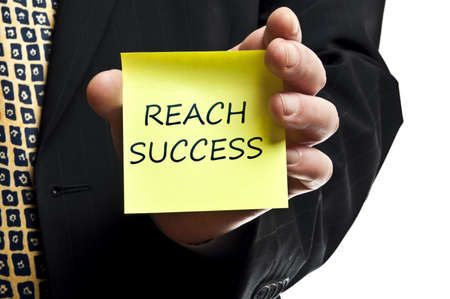 Reach succes post it in business man hand photo