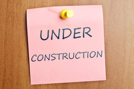 Under construction word post it on wooden wall photo