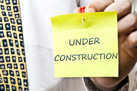 Under construction post it in business man hand photo