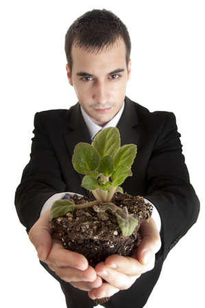 Isolated business man holding a plant photo