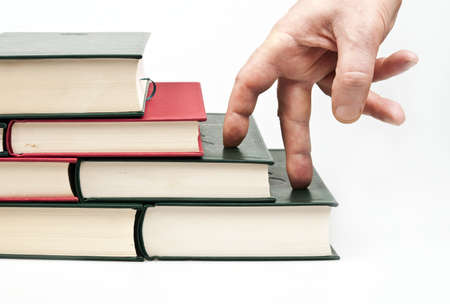 knowledge concept: Finger climbing books on white