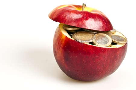 dinero euros: Muchas monedas dentro de manzana roja Foto de archivo
