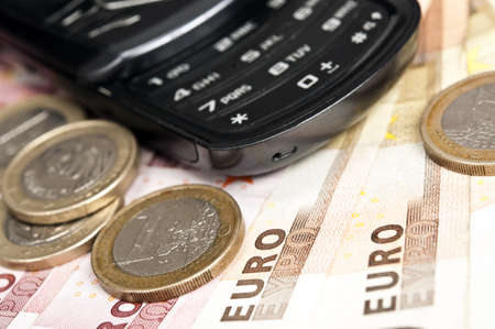 Banknotes and coins near phone Stock Photo - 9222121