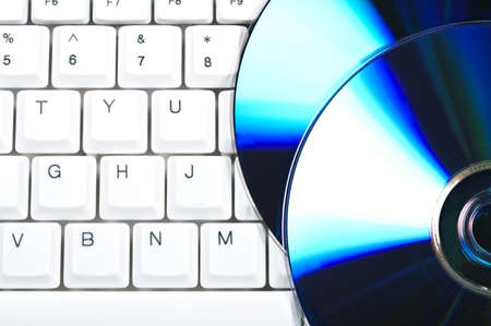 computer software: Cd on computer white keyboard Stock Photo