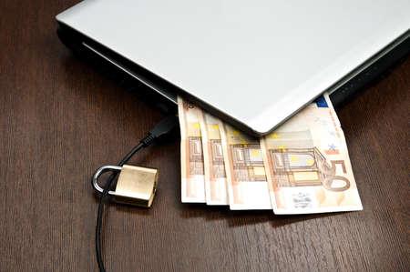 Closeup to laptop and euro banknotes photo